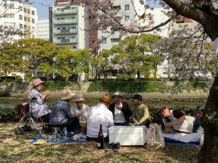 Senior citizens enjoying a picnic by a canal.
