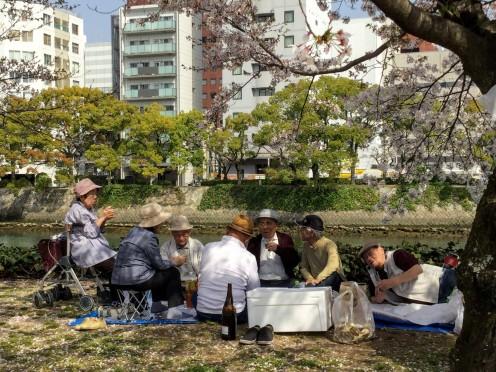 Senior citizens enjoying a picnic by a canal.