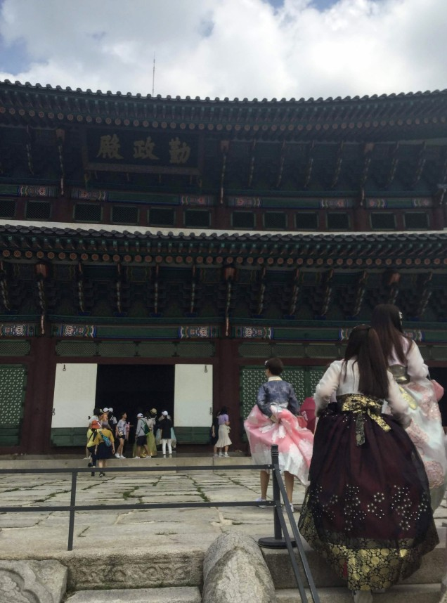 Girls in hanbok climb the stairs to the main palace building. Shot on iphone.